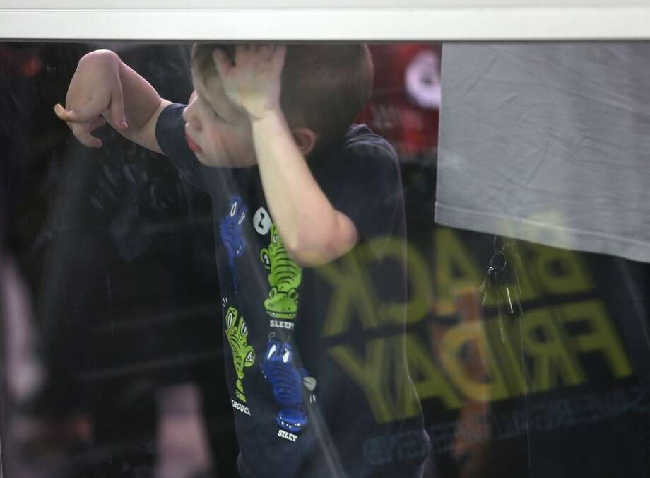 A boy looks through a door while standing in line for holiday shopping at Best Buy on Thursday, Nov. 26, 2015, in Panama City, Fla. (Patti Blake/News Herald via AP) MANDATORY CREDIT