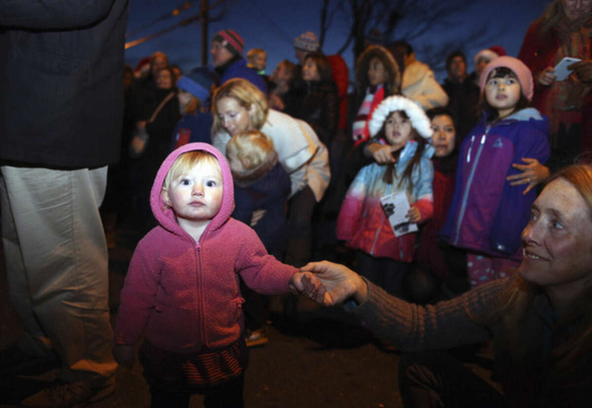 Amelia Waters, 1, listens to the BMHS Carolers at the Light Up Rowayton event Sunday evening. Hour Photo / Danielle Calloway