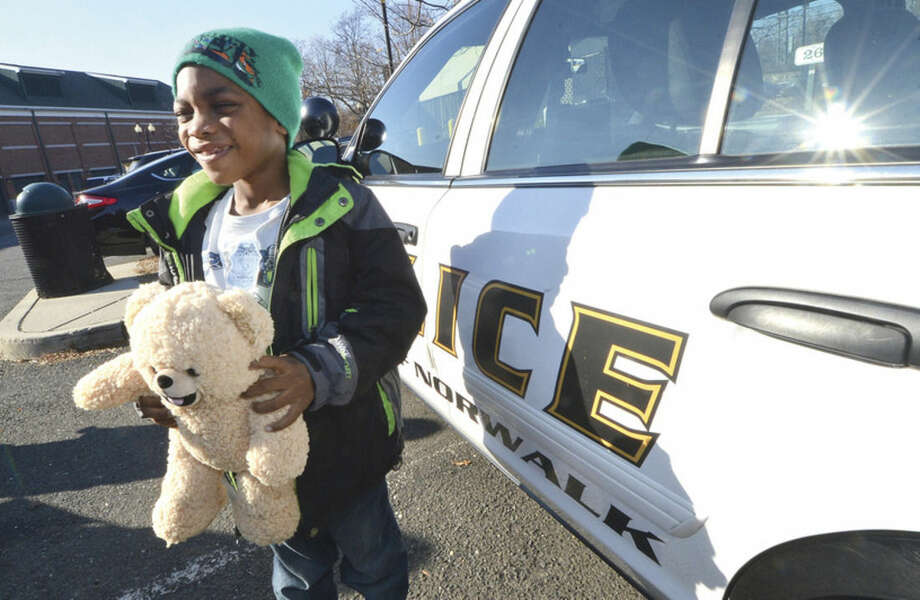 Hour Photo/Alex von KleydorffCornezz McCreae, 5, is given a Teddy Bear from one of the Norwalk Police Departments cruisers