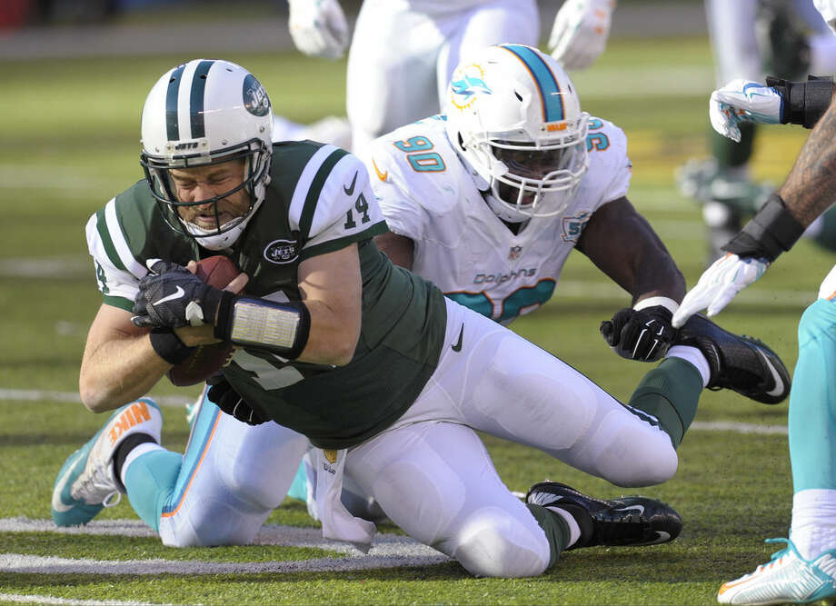 New York Jets quarterback Ryan Fitzpatrick (14) dives to avoid a tackle by Miami Dolphins' Earl Mitchell (90) during the first half of an NFL football game Sunday, Nov. 29, 2015, in East Rutherford, N.J. (AP Photo/Bill Kostroun)