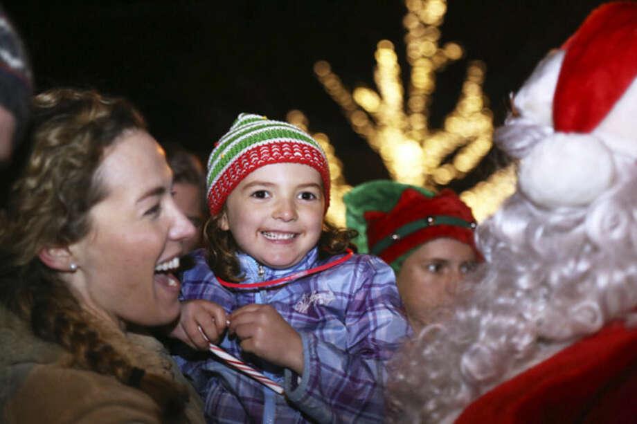 Hour photo/Danielle CallowayBess Wayland, 5 1⁄2, meets Santa at the Light Up Rowayton event Sunday evening.