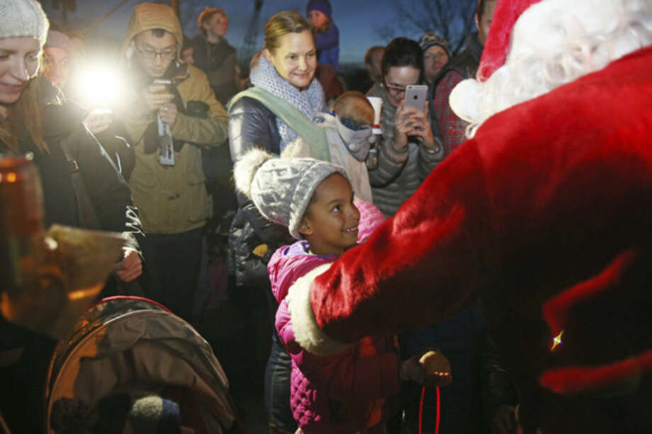 Hour photo/Danielle CallowayAbove, Keira Penn, 5, meets Santa at the Light Up Rowayton event Sunday evening. Below, Santa mingles with guests at the Light Up Rowayton event.