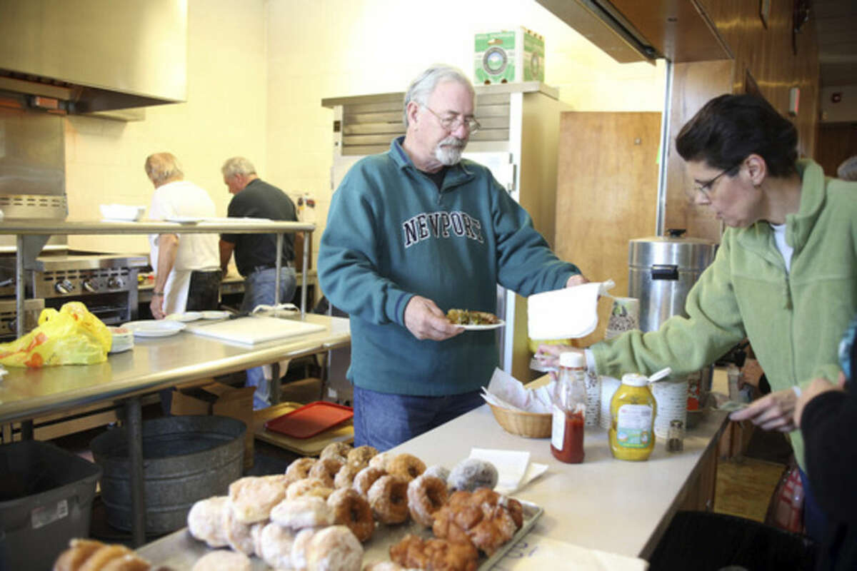 John Fusco serves up some sausage and peppers during the American Legion Holiday Fair on County Street in Norwalk Sunday afternoon. Hour Photo / Danielle Calloway