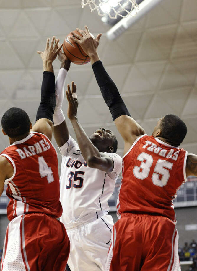 Houston's TaShawn Thomas, right, blocks a shot attempt by Connecticut's Amida Brimah, as Houston's LeRon Barnes, left, defends during the first half of an NCAA college basketball game, Thursday, Jan. 30, 2014, in Storrs, Conn. (AP Photo/Jessica Hill)