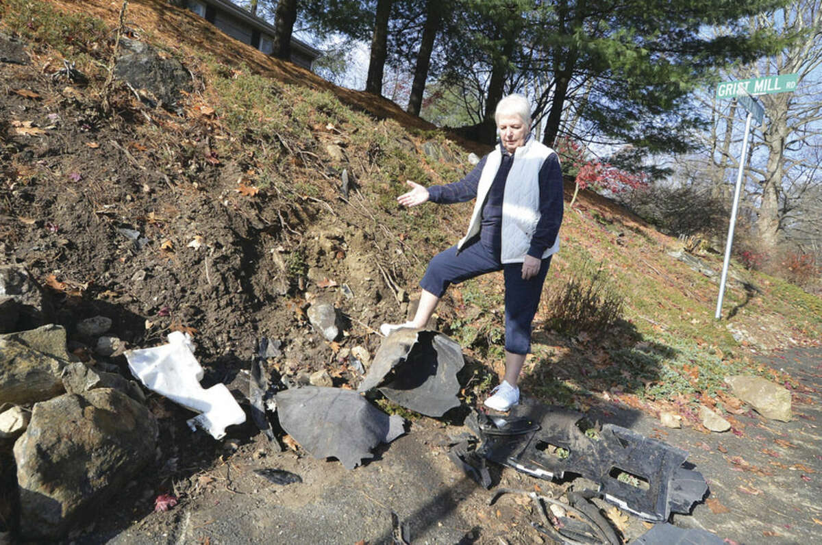 Hour Photo/Alex von Kleydorff Norwalk resident Barbara Robinson stands over car parts left after a car crashed into the front of her property at the corner of Belden Hill Rd and Grist Mill.