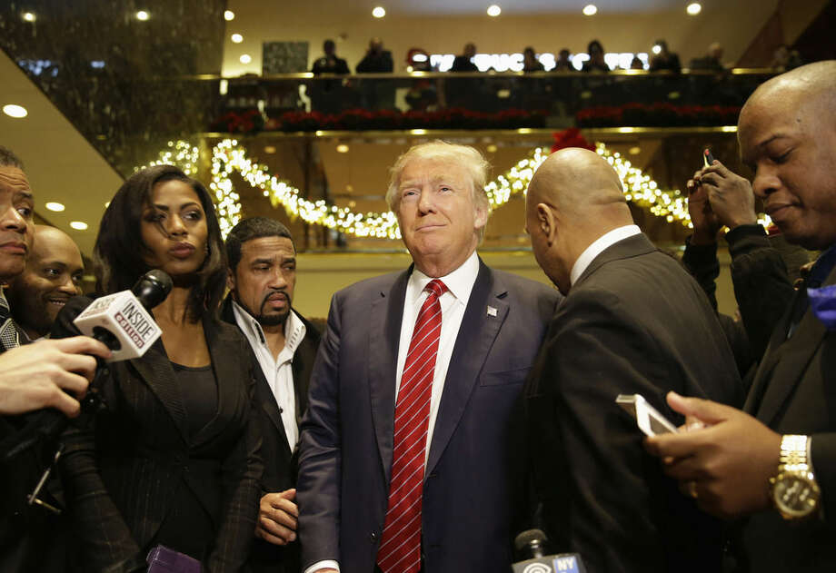 Republican Presidential candidate Donald Trump, center, joins a group of African-American religious leaders to speak to reporters in New York, Monday, Nov. 30, 2015. Trump met with a coalition of 100 African-American evangelical pastors and religious leaders in a private meeting at Trump Tower. (AP Photo/Seth Wenig)