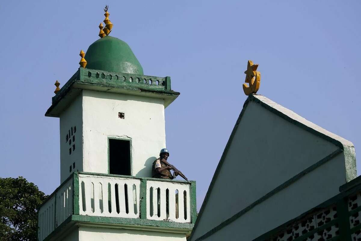 A UN soldier stands guard on the top of Central Mosque on the occasion of Pope Francis visit in Bangui's Muslim enclave of PK5, Central African Republic, Monday Nov. 30, 2015. The Pope was welcomed by a crowd of people and prayed inside the Central Mosque. (AP Photo/Jerome Delay)