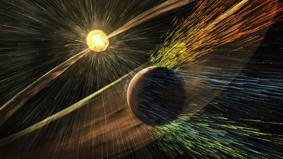 This image made available by NASA on Thursday, Nov. 5, 2015 shows an artist's rendering of a solar storm hitting the planet Mars and stripping ions from the planet's upper atmosphere. NASA's Mars-orbiting Maven spacecraft has discovered that the sun robbed the red planet of its once-thick atmosphere and water. On Thursday, scientists reported that even today, the solar wind is stripping away about 100 grams of atmospheric gas every second. (Goddard Space Flight Center/NASA via AP)