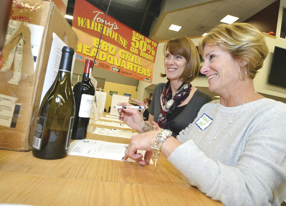 Hour Photo/Alex von Kleydorff Norwalk Education Foundation Interim Executive Director Marge Costa and Gina Krasnavage bid on some of the silent auction items during the foundations Taste for education event at Aitoro's in Norwalk