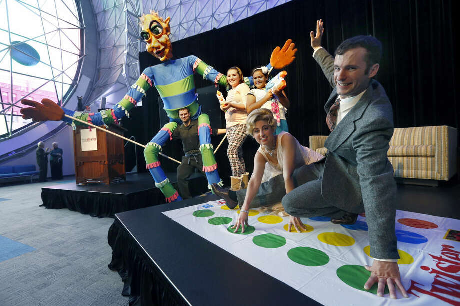 Rochester residents Lauren Sodano and Shawn Gray, right, portray Eva Gabor and Johnny Carson, playing Twister; as Haley Smith,11, of Henrietta, and Estefania Muñoz, 9, of Greece play with Super Soakers along side Peter Fekete, left, of Syracuse, of the Open Hand Theater, holding a giant puppet at the National Toy Hall of Fame announcement Thursday, Nov. 5, 2015, in Rochester, N.Y. Twister, the parlor game once too hot for the Sears catalog but cool enough for Johnny Carson, along with the Super Soaker and puppet were inducted into the National Toy Hall of Fame Thursday. (Carlos Ortiz/Democrat & Chronicle via AP) MAGS OUT; NO SALES; MANDATORY CREDIT