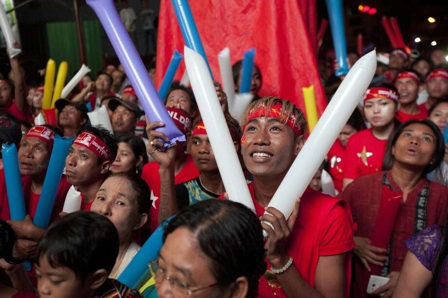 Supporters of Myanmar opposition leader Aung San Suu Kyi's National League for Democracy party cheer as they watch the results of the general election on an LED screen displayed outside the party's headquarters Monday, Nov. 9 2015 in Yangon, Myanmar. Myanmar voted Sunday in historic elections that will test whether popular mandate can loosen the military's longstanding grip on power, even if opposition leader Aung San Suu Kyi's party secures a widely-expected victory. (AP Photo/Khin Maung Win)