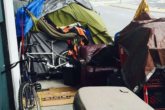 This homeless encampment on Essex Street has a tent, bike and leather armchair