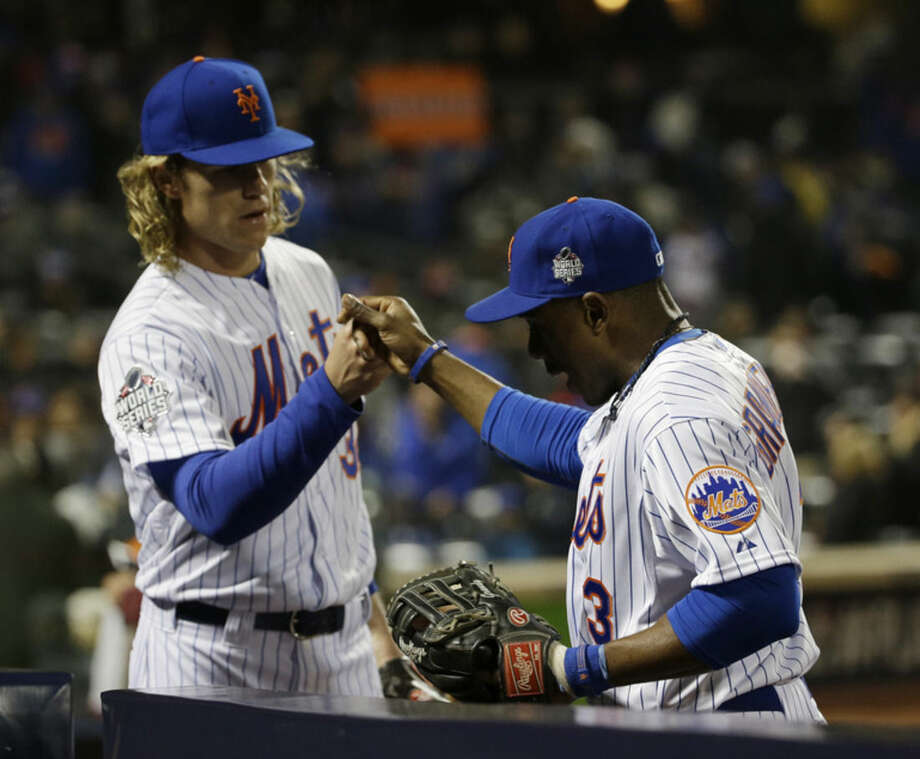 New York Mets pitcher Noah Syndergaard congratulates teammate Curtis Granderson after a catch during the fifth inning of Game 3 of the Major League Baseball World Series against the Kansas City Royals Friday, Oct. 30, 2015, in New York. (AP Photo/David J. Phillip)