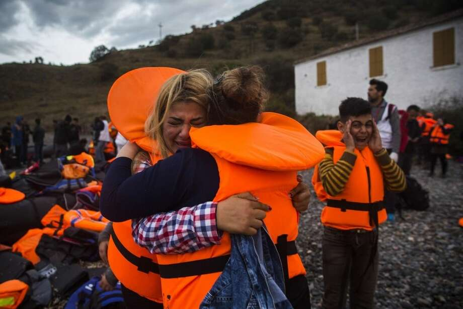 Two women hug each other as a boy cries after their arrival from the Turkish coast to the Greek island of Lesbos, Thursday, Oct. 29, 2015. Europe's largest refugee crisis since World War II is entering a perilous and uncharted phase, as the usual pattern of migrant season ending by autumn is overturned by intensifying fighting in Syria and overcrowding in refugee centers in Turkey and Lebanon. (AP Photo/Santi Palacios)