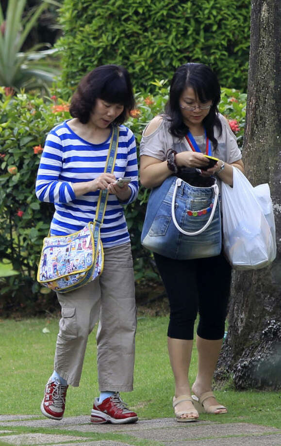 A Chinese relative, left, of passengers aboard a missing Malaysia Airlines plane walks with a counselor at a resort in Cyberjaya, Malaysia, Friday, March 21, 2014. Search planes flying out of Australia on Friday began a difficult hunt through rough seas in one of the remotest places on Earth for objects that may be from the missing Malaysia Airlines plane. (AP Photo/Lai Seng Sin)