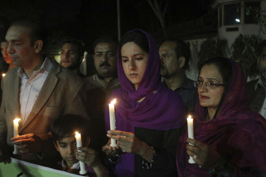 "Pakistanis hold candles for the passengers of a Malaysia Airlines plane which disappeared on March 8, while holding a candlelight vigil organized by Peace for Life Welfare Foundation in Lahore, Pakistan, Thursday, March 20, 2014. An air search in the southern Indian Ocean for possible objects from the missing Malaysia Airlines plane described as the ""best lead"" so far ended for the day without success Thursday but will resume in the morning, Australian rescue officials said. (AP Photo/K.M. Chaudary)"