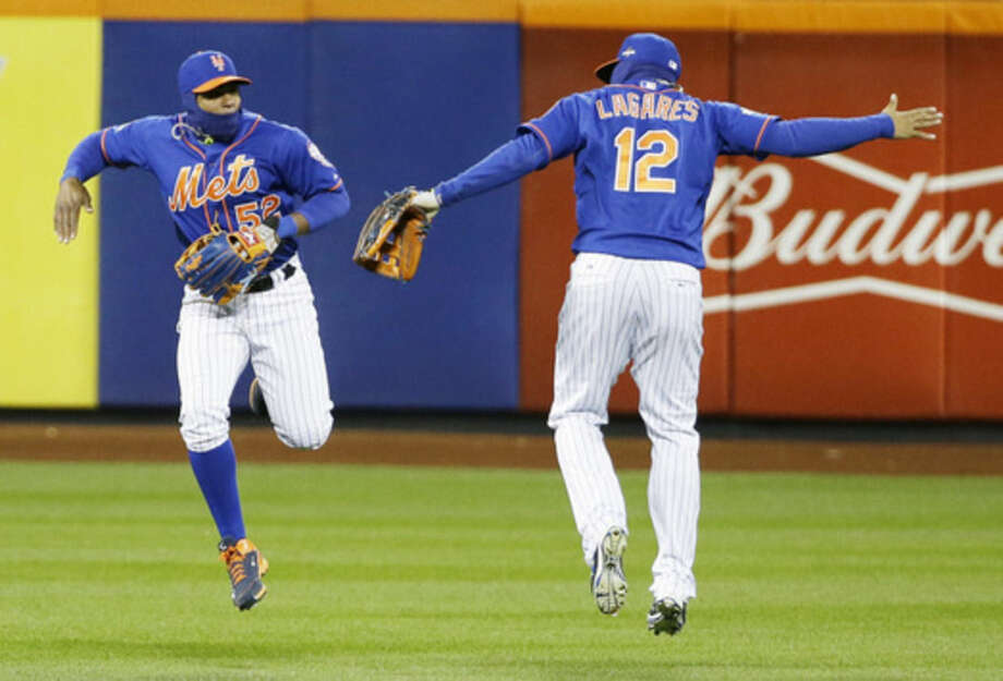 New York Mets' Yoenis Cespedes (52) and Juan Lagares (12) celebrate after Game 2 of the National League baseball championship series against the Chicago Cubs Sunday, Oct. 18, 2015, in New York. The Mets won 4-1 to take a 2-0 lead in the series. (AP Photo/David J. Phillip)