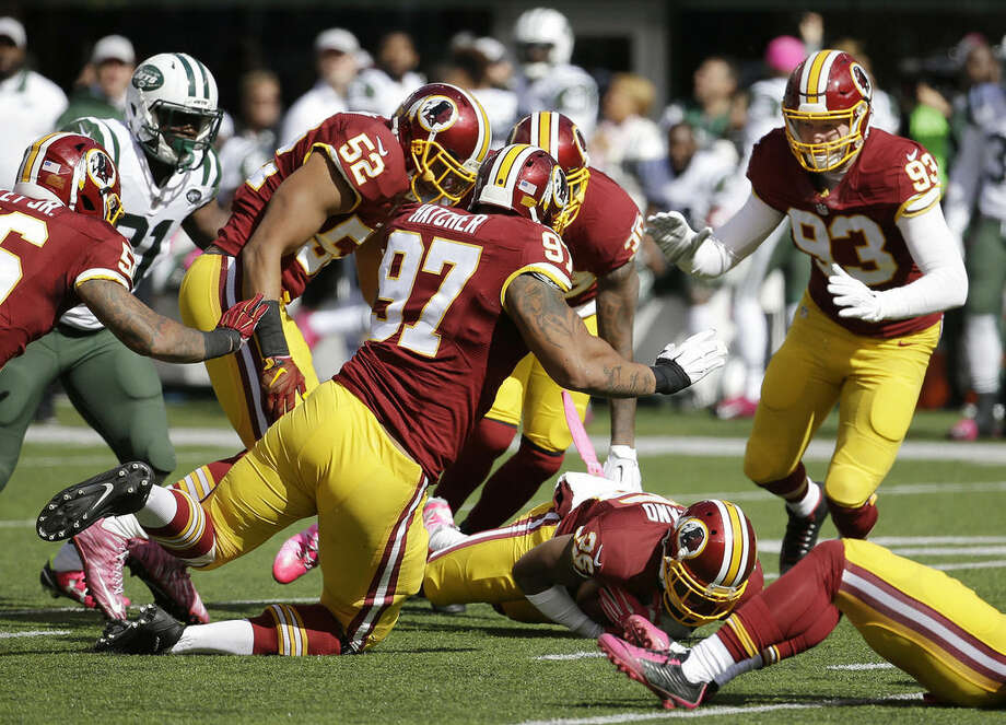 Washington Redskins cornerback Bashaud Breeland, bottom, falls on the football to recover a fumble by New York Jets wide receiver Eric Decker (not shown) during the first half of an NFL football game, Sunday, Oct. 18, 2015, in East Rutherford, N.J. (AP Photo/Seth Wenig)
