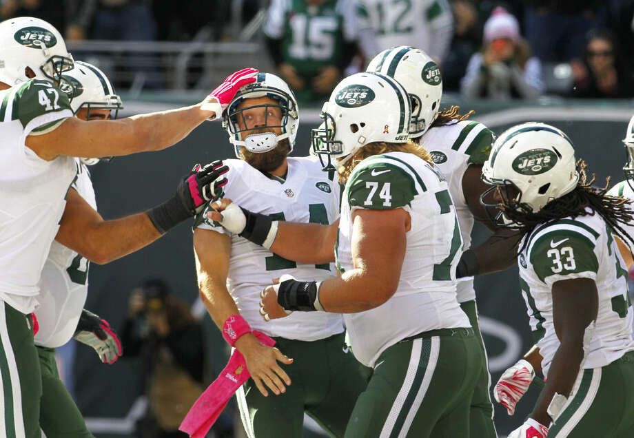 New York Jets quarterback Ryan Fitzpatrick, center left, is mobbed by teammates after scoring a touchdown run against the Washington Redskins during the second half of an NFL football game, Sunday, Oct. 18, 2015, in East Rutherford, N.J. (AP Photo/Gary Hershorn)