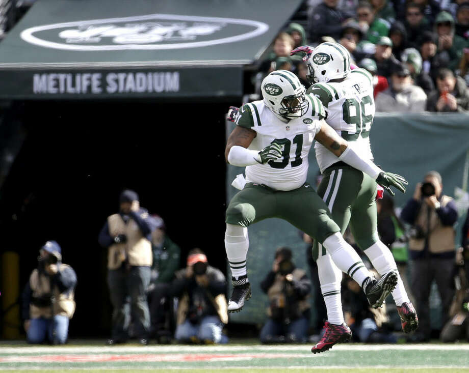 New York Jets defensive end Sheldon Richardson (91) and defensive end Muhammad Wilkerson (96) celebrate after Richardson sacked Washington Redskins quarterback Kirk Cousins during the first half of an NFL football game, Sunday, Oct. 18, 2015, in East Rutherford, N.J. (AP Photo/Seth Wenig)