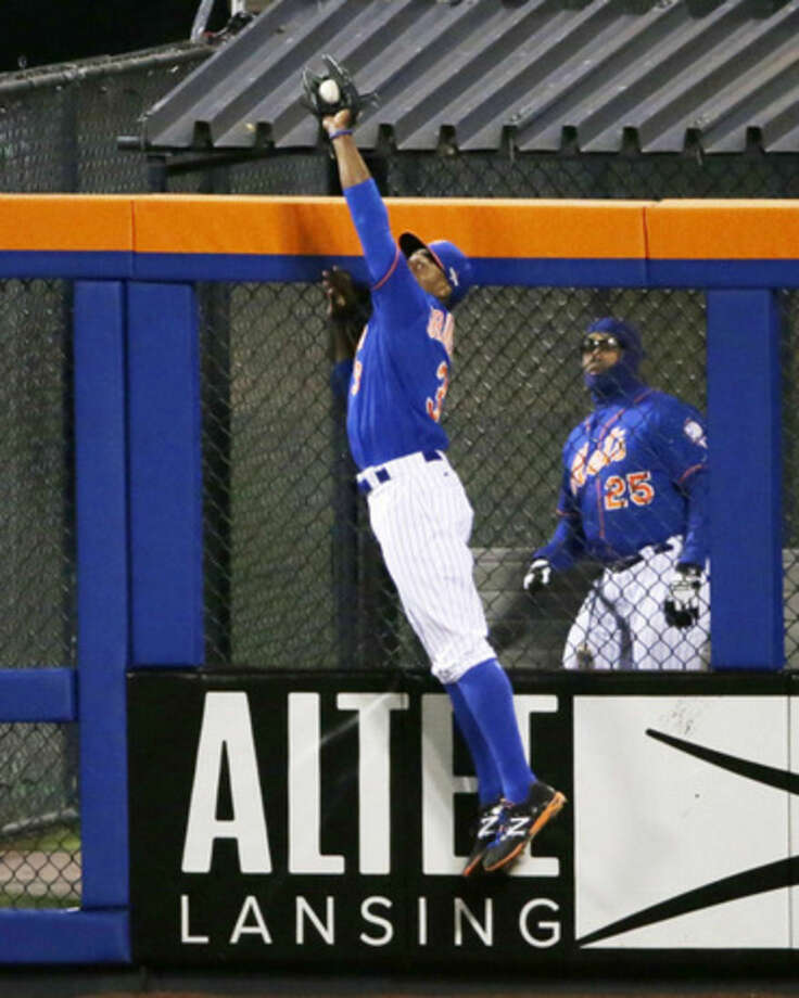 New York Mets' Curtis Granderson catches a ball at the wall hit by Chicago Cubs' Chris Coghlan during the second inning of Game 2 of the National League baseball championship series Sunday, Oct. 18, 2015, in New York. (AP Photo/Frank Franklin II)