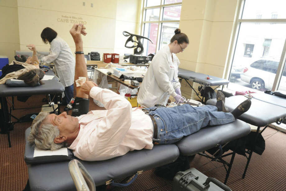 Hour photo/Matthew VinciJohn Droy donates blood with American Red cross R.N. Jamie Pellitier Sunday at the Palace Theatre where the Red Cross blood drive was held. Everyone who donated was entered for a chance to win a pair of tickets to II Volo at the theatre on June 14.