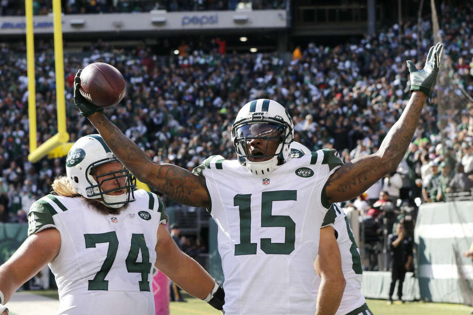 New York Jets wide receiver Brandon Marshall (15) celebrates with teammates Nick Mangold (74) and Eric Decker (87) after scoring on a touchdown pass from quarterback Ryan Fitzpatrick, not pictured, during the second half of an NFL football game against the Washington Redskins, Sunday, Oct. 18, 2015, in East Rutherford, N.J. (AP Photo/Gary Hershorn)