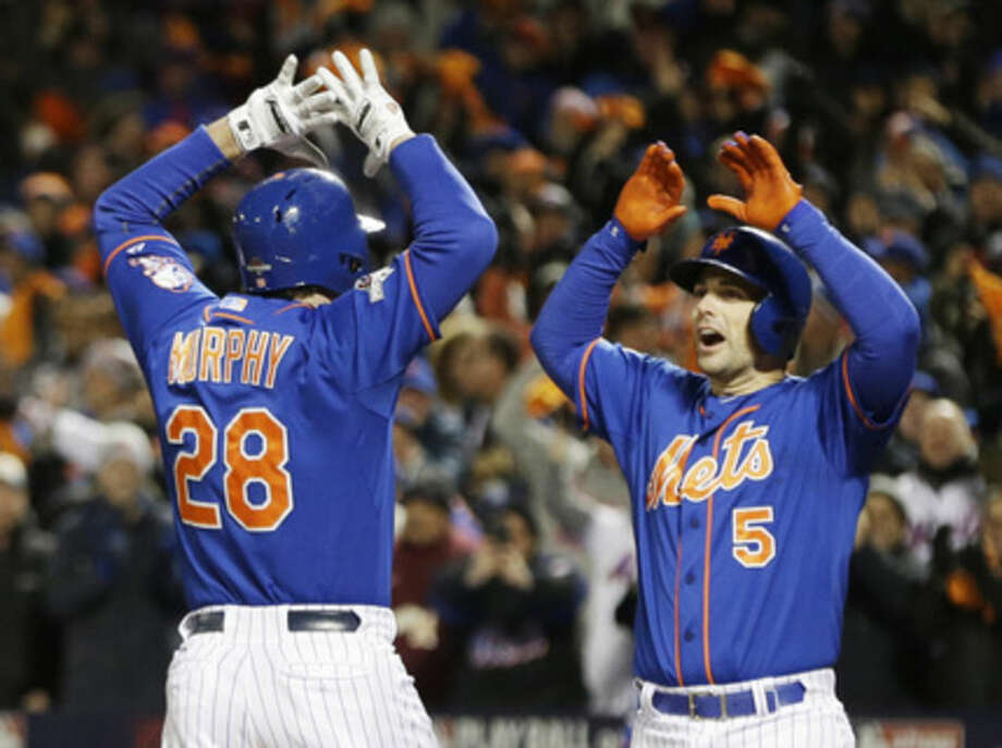 New York Mets' Daniel Murphy is congratulated by teammate David Wright after hitting a two-run home run during the first inning of Game 2 of the National League baseball championship series against the Chicago Cubs Sunday, Oct. 18, 2015, in New York. (AP Photo/David J. Phillip)