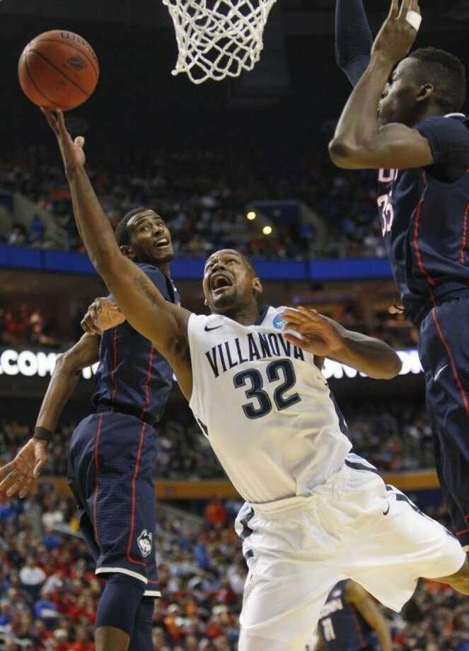Villanova's James Bell (32) drives past Connecticut's Amida Brimah (35) during the first half of a third-round game in the NCAA men's college basketball tournament in Buffalo, N.Y., Saturday, March 22, 2014. (AP Photo/Bill Wippert)