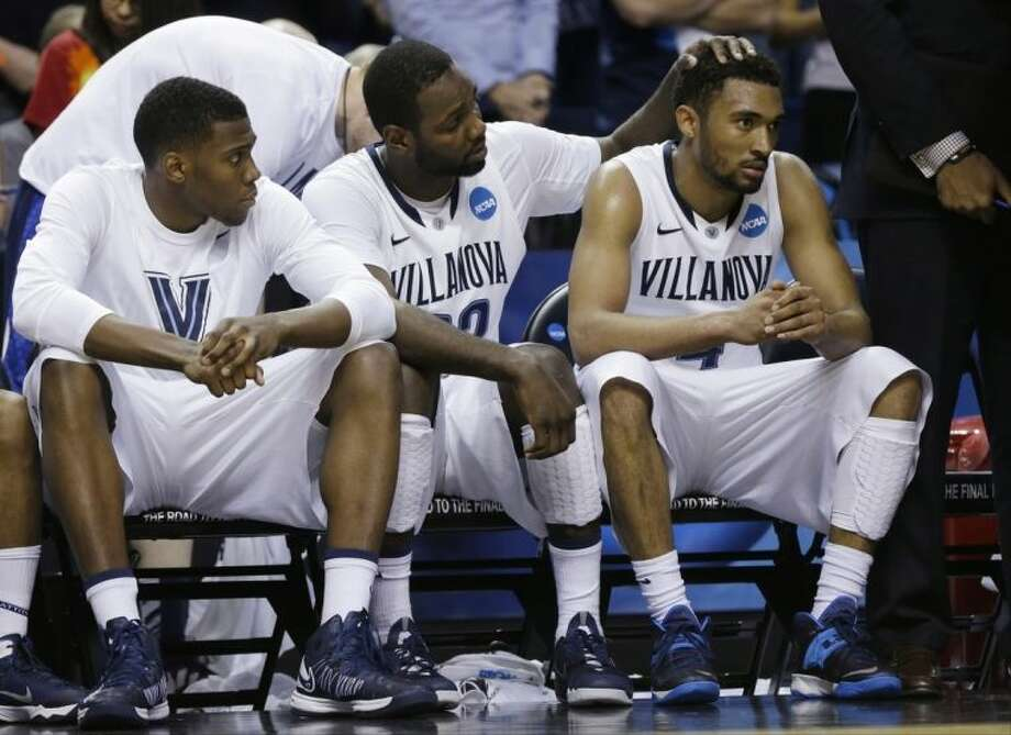 Villanova's JayVaughn Pinkston (22) and Darrun Hilliard II (4) react with teammates during the second half of a third-round game in the NCAA men's college basketball tournament in Buffalo, N.Y., Sunday, March 23, 2014. (AP Photo/Frank Franklin II)