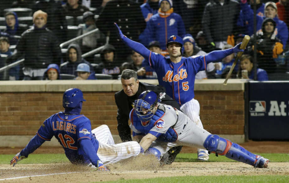 New York Mets' Juan Lagares slides safely under the tag of Chicago Cubs catcher Miguel Montero during the seventh inning of Game 1 of the National League baseball championship series Saturday, Oct. 17, 2015, in New York. Lagares scored from third on a sacrifice fly by Curtis Granderson. (AP Photo/David J. Phillip)