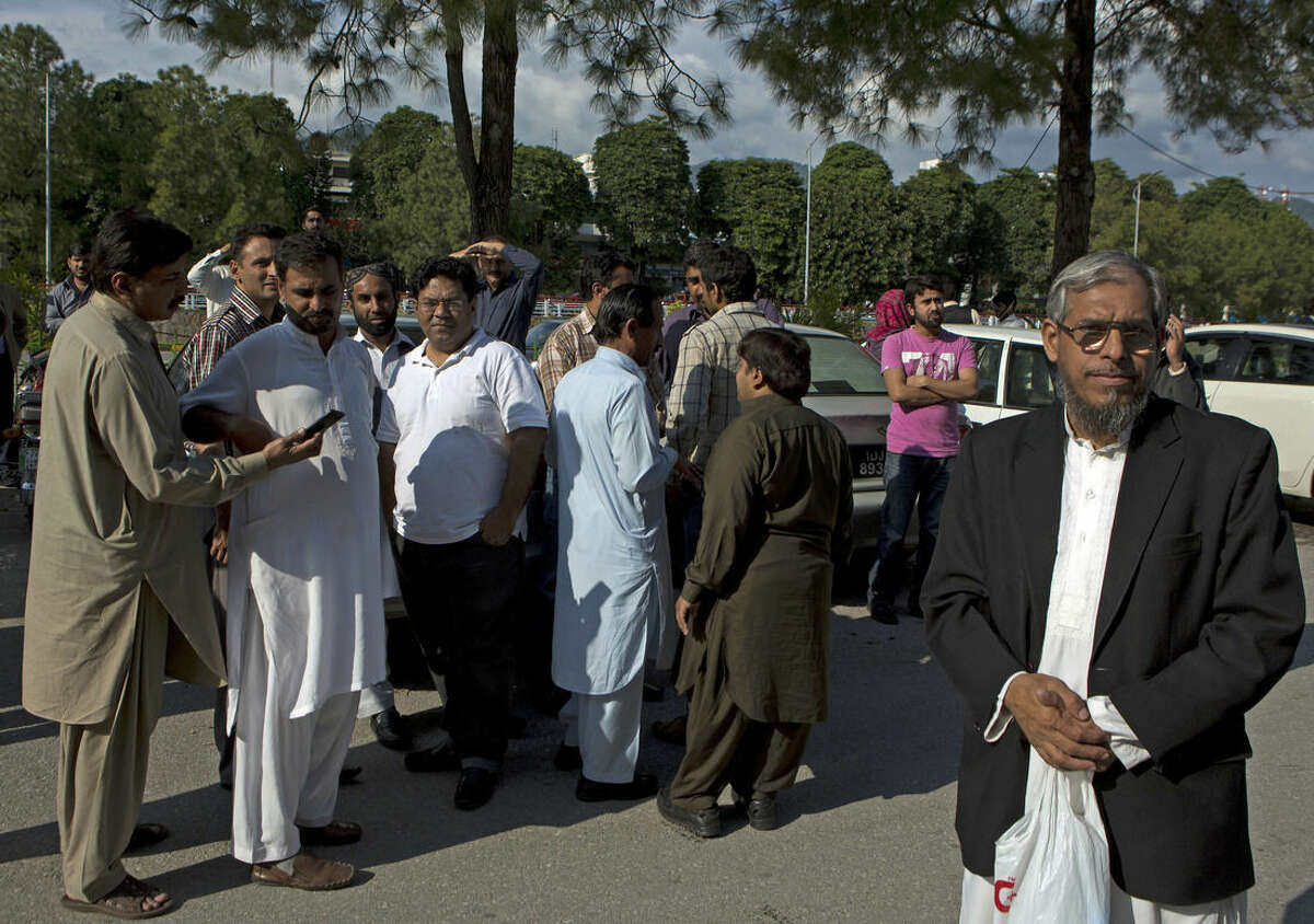 People stand outside their offices after a severe earthquake is felt in Islamabad, Pakistan, Monday, Oct. 26, 2015. A powerful 7.7-magnitude earthquake in northern Afghanistan was felt across much of South Asia on Monday, shaking buildings from Kabul to Delhi and cutting power and communications in some areas. In the Pakistani capital, walls swayed back and forth and people poured out of office buildings in a panic, with many reciting verses from the Quran. (AP Photo/B.K. Bangash)