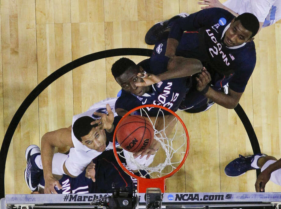 Connecticut's Amida Brimah (35) and Connecticut's DeAndre Daniels (2) and Villanova's Josh Hart look for a rebound during the first half of a third-round game in the NCAA men's college basketball tournament in Buffalo, N.Y., Saturday, March 22, 2014. (AP Photo/Bill Wippert)