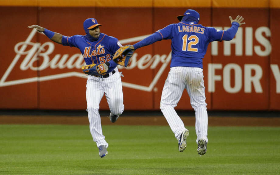 New York Mets' Yoenis Cespedes (52) and Juan Lagares (12) celebrate after Game 1 of the National League baseball championship series against the Chicago Cubs Saturday, Oct. 17, 2015, in New York. The Mets won 4-2 to take a 1-0 lead in the series. (AP Photo/David J. Phillip)