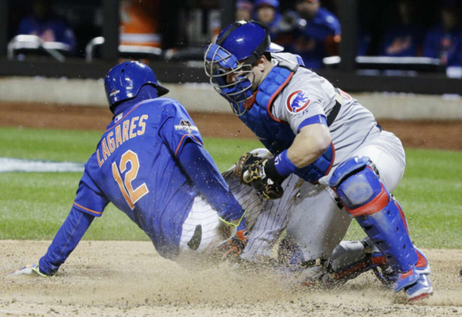 New York Mets' Juan Lagares slides safely under the tag of Chicago Cubs catcher Miguel Montero during the seventh inning of Game 1 of the National League baseball championship series Saturday, Oct. 17, 2015, in New York. Lagares scored from third on a sacrifice fly by Curtis Granderson. (AP Photo/Julie Jacobson)