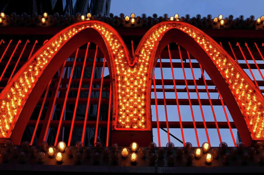 """This Sunday, Jan. 10, 2016, photo shows the sign on the McDonald's on 42nd Street near Times Square in New York. McDonald's is moving back to Chicago and into the old home of """"The Oprah Winfrey Show."""" The world's biggest hamburger chain says it signed a lease to move its corporate headquarters from the leafy suburbs of Oak Brook, Ill., to downtown Chicago in 2018. McDonald's was previously based in the city from 1955 to 1971. (AP Photo/Gene J. Puskar) Photo: Gene J. Puskar, STF / Associated Press / AP"""