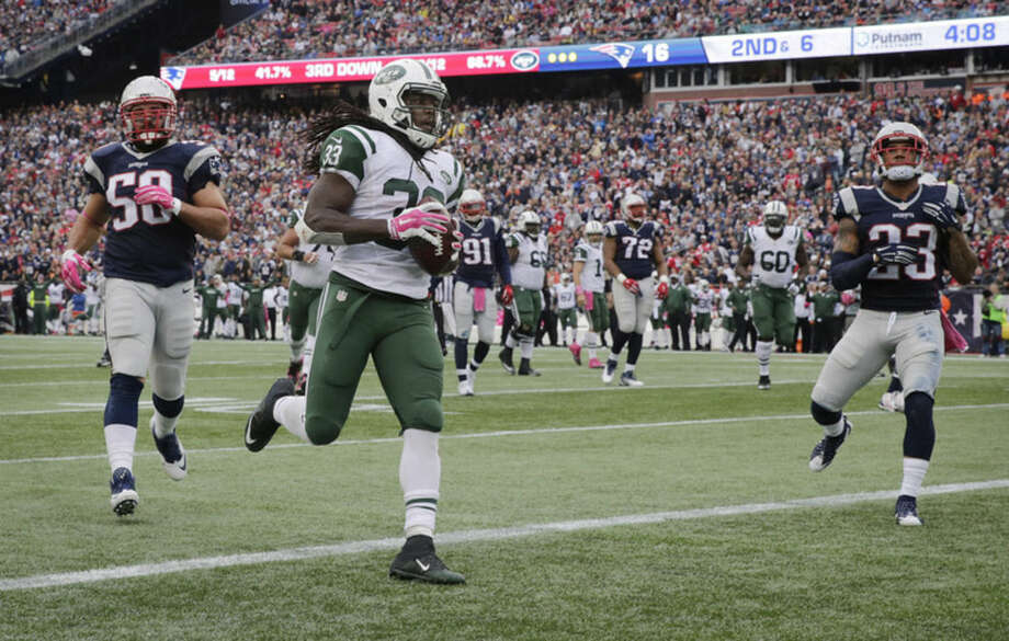 New York Jets running back Chris Ivory (33) scores a touchdown as New England Patriots defenders Rob Ninkovich (50) and Devin McCourty (32) give chase during the second half of an NFL football game, Sunday, Oct. 25, 2015, in Foxborough, Mass. (AP Photo/Charles Krupa)