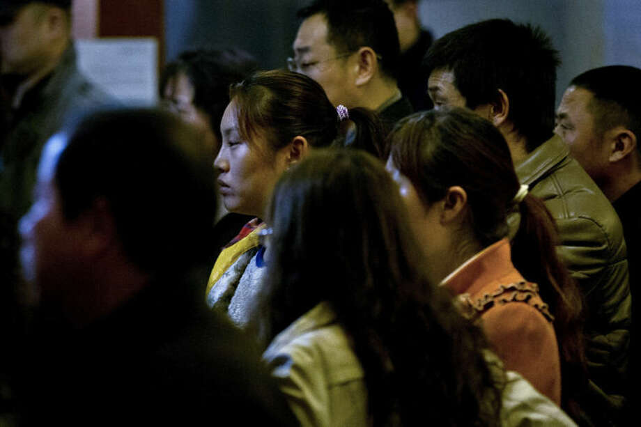 Relatives of Chinese passengers aboard missing Malaysia Airlines Flight MH370 watch a TV news program about the missing flight after they attended a briefing meeting with Malaysian officials in a hotel ballroom in Beijing, China, Friday, March 21, 2014. (AP Photo/Alexander F. Yuan)