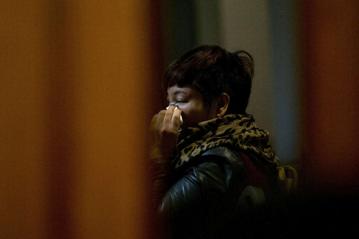 One of the relatives of Chinese passengers aboard missing Malaysia Airlines Flight MH370 wipes her tears as she watches a TV news program about the missing flight after a briefing meeting with Malaysian officials in a hotel ballroom in Beijing, China, Friday, March 21, 2014. Planes are flying out of Australia again to search for two objects detected by satellite that may be debris from the missing Malaysian airliner. (AP Photo/Alexander F. Yuan)