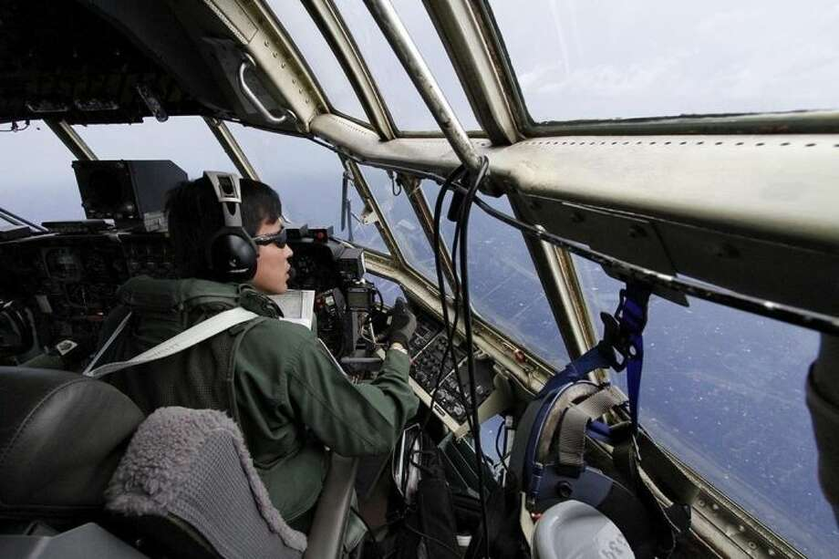 AP photo / Koji UedaJapanese Air Self-Defense Force copilot Ryutaro Hamahira scans the ocean aboard a C130 aircraft while it flies over the southern search area in the southeastern Indian Ocean, 200 to 300 kilometers (124 to 186 miles) south of Sumatra, Indonesia Friday.