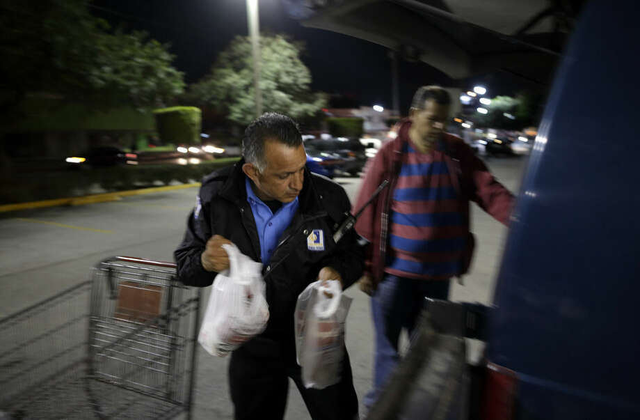 Security guard Guillermo Soria, left, helps a customer while working in front of a Smart & Final store Wednesday, Nov. 18, 2015, in Tijuana, Mexico. After living for nearly 25 years in the United States, Soria returned to Mexico and found work as a security guard. A new study finds more Mexicans are leaving the United States than coming to the country, marking a reversal to one of the most significant immigration trends in U.S. history. (AP Photo/Gregory Bull)