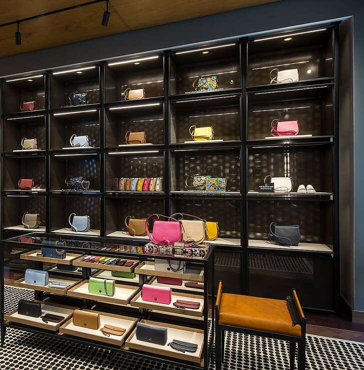 The Coach store (190 Post St.) has revamped its look with new dark wood flooring, area carpets, fuzzy armchairs and dark shelving allow brightly colored handbags and clothing to pop like neon book bindings stacked on library shelves, both at street level and one floor below.