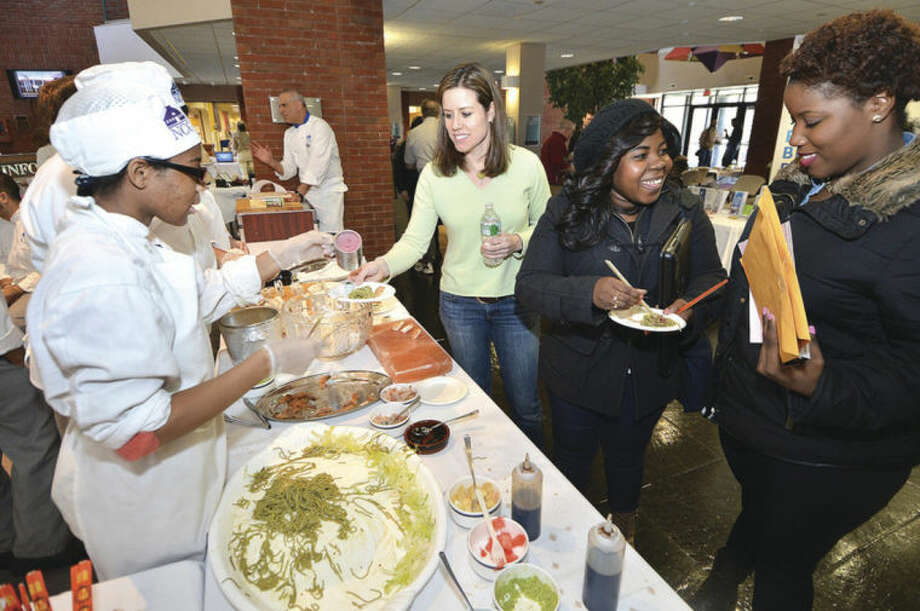 Hour Photo/Alex von Kleydorff Angel McCray along with others from the Culinary Arts Program serve some Green Tea Soba noodles with beet powder and fresh made sushi and Sashimi to promote heathly diets at the NCC Health Fair