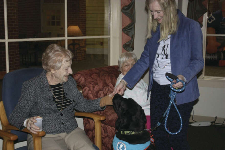 Residents Dorothy Peisinger and Rose Pirie interact with Bingo, accompanied by Diane Muldowney.Contributed photo