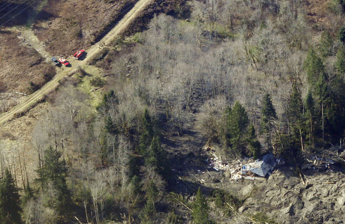 Emergency vehicles are shown parked on a road leading to the remains of a house destroyed by the massive mudslide that killed at least eight people Saturday and left dozens missing, as shown in this aerial photo, Monday, March 24, 2014, near Arlington, Wash. The search for survivors grew Monday, raising fears that the death toll could climb far beyond the eight confirmed fatalities. (AP Photo/Ted S. Warren)