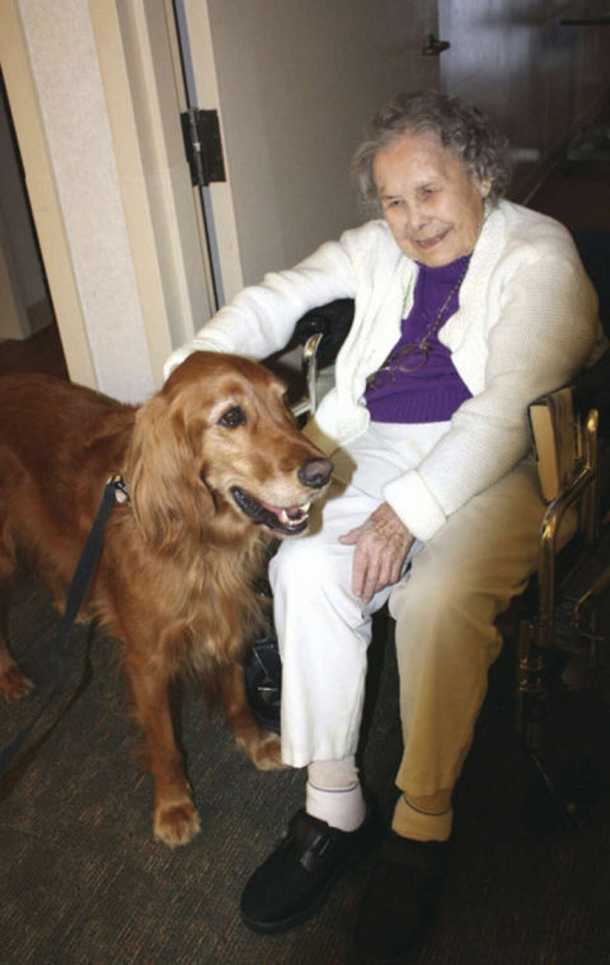 Resident Elma Fay pets Meca. Contributed photo