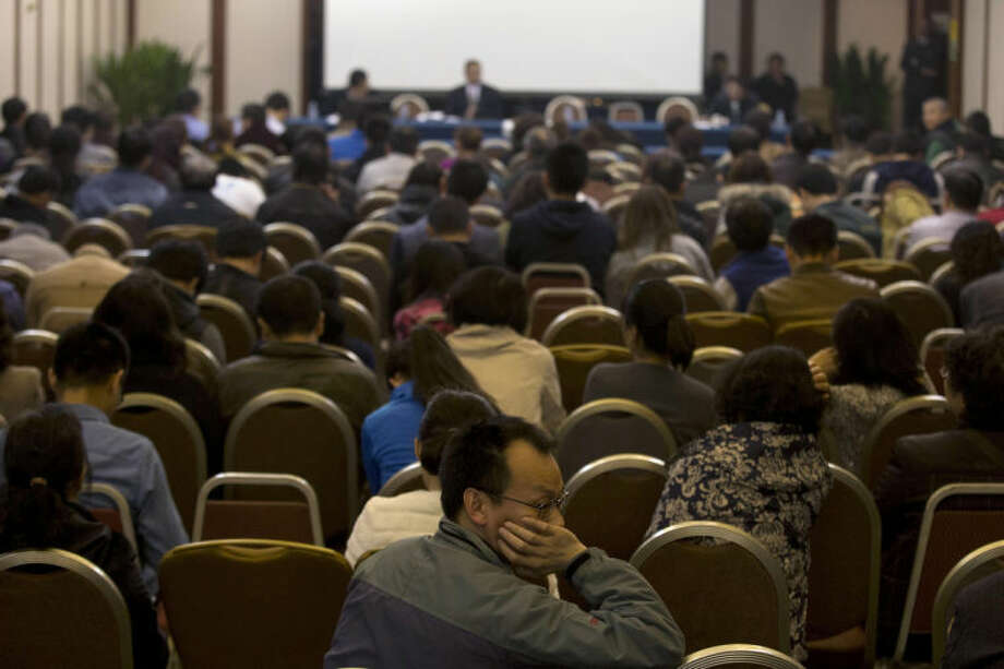 Relatives of Chinese passengers aboard the missing Malaysia Airlines flight MH370 attend a meeting with the Malaysian ambassador to China and a representative of Malaysia Airlines in Beijing, China, Monday, March 24, 2014. Rain was expected to hamper the hunt Monday for debris suspected of being from the missing Malaysia Airlines jet, as the United States prepared to move a specialized device that can locate black boxes into the south Indian Ocean region. (AP Photo/Ng Han Guan)