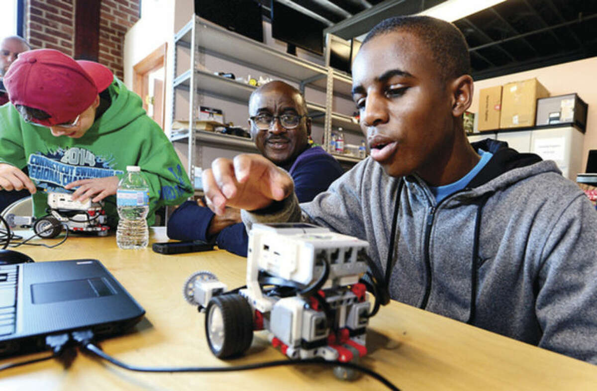 Hour photo / Erik Trautmann Josh Mitchell, 15, and his dad, Maurice Mitchell, learn to program a robot to navigate an obstacle course and complete various challenges using EV3 programming software during the Intro to Robotics with Lego Mindstorms at the Fairfield County Makers' Guild in Norwalk Saturday.