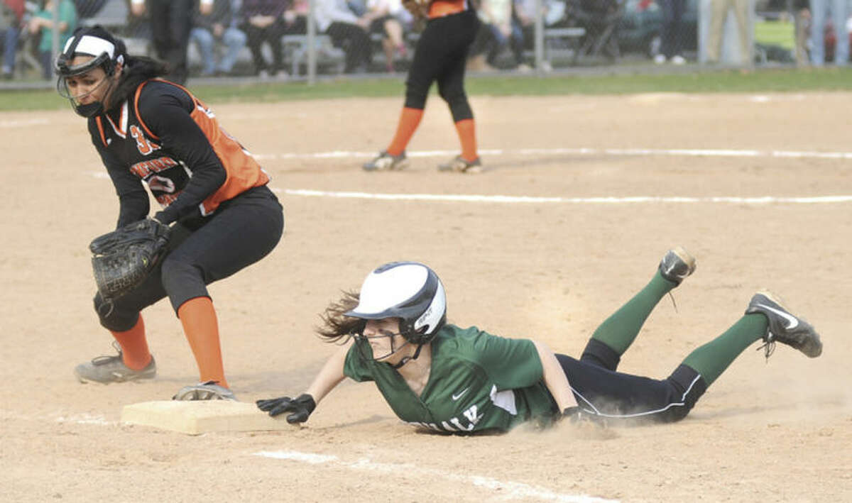 Hour photo/John Nash Norwalk's Kasey Hogan, right, dives back to first base during Friday afternoon's game, while Stamford's Brianna Arias holds her on.