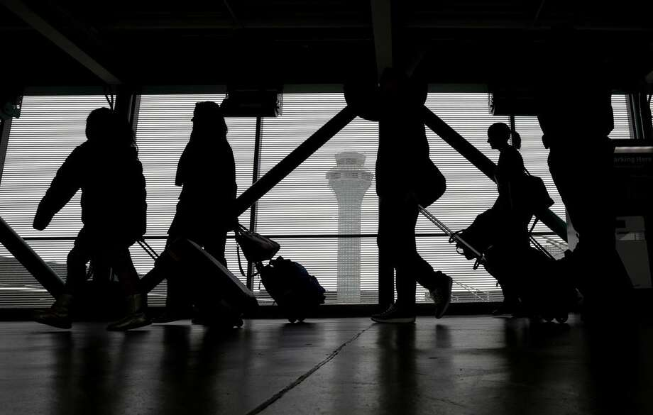 Passengers walk through Terminal 3 at O'Hare International Airport on Saturday, Nov. 21, 2015, in Chicago. The first significant snowstorm of the season blanketed some parts of the Midwest with more than a foot of snow and more was on the way Saturday, creating hazardous travel conditions and flight delays. (AP Photo/Nam Y. Huh)